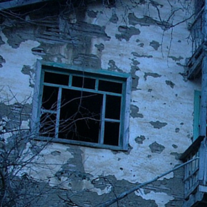 exterior wall of a house with fading white paint