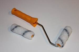 Paint roller with orange handle and an extra roller brush