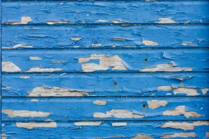 a wall with blue paint that is peel in some areas